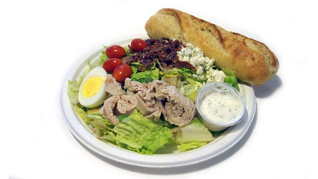 Cobb Salad: romaine, roast turkey, grape tomatoes, blue cheese, bacon, hard boiled egg, with ranch dressing.
