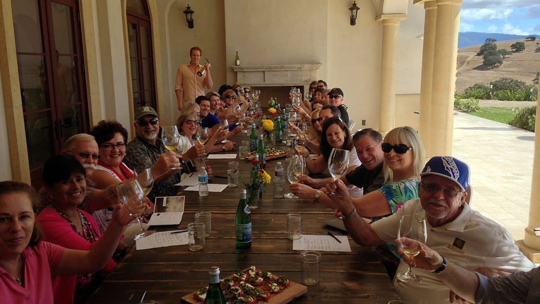 a seated group of wine tasters at a wine estate making a toast.