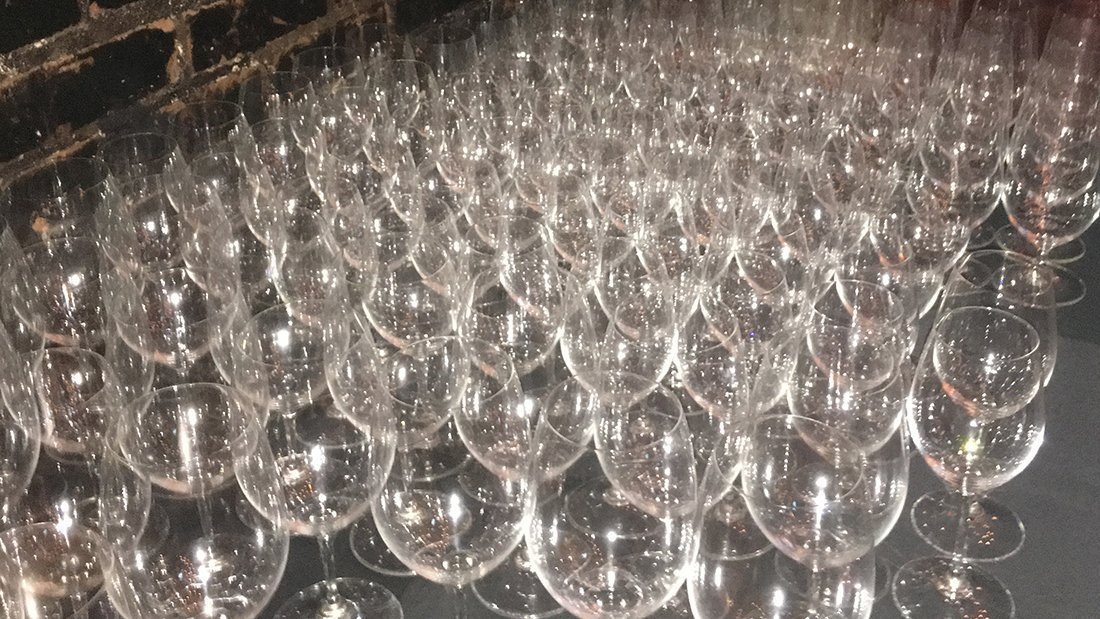 Many wine glasses ready for wine tasters.