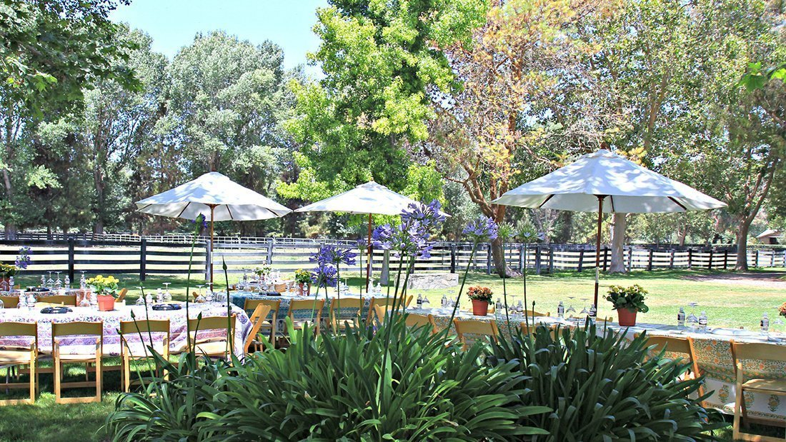 A picture of tables and umbrellas set for a wine tasting and lunch at a private horse ranch.