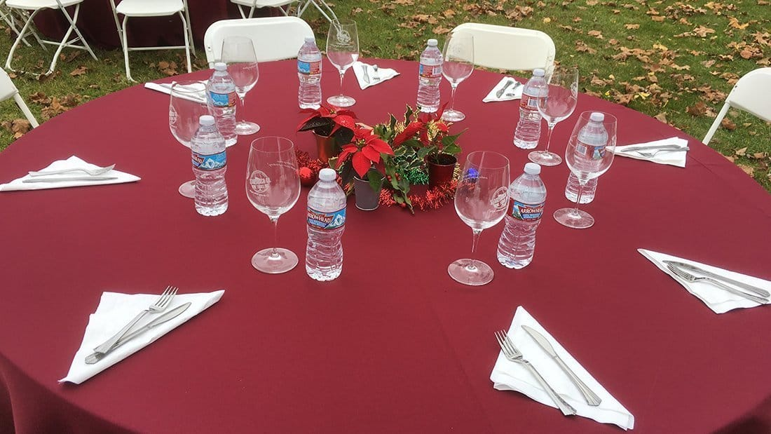 A red tablecloth covered table with tableware, glasses, waters, and a seasonal decoration.