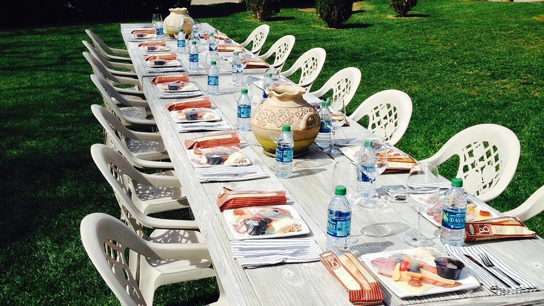A long outdoor table with the lunches served and ready to eat.