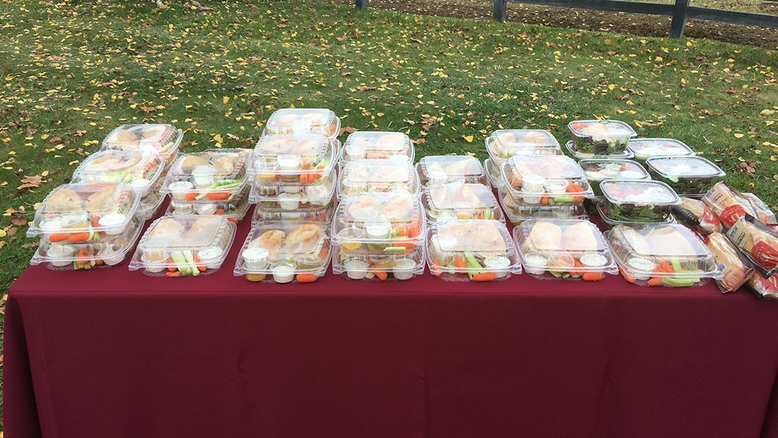 A table with dozens of box lunches ready for the guests to consume.