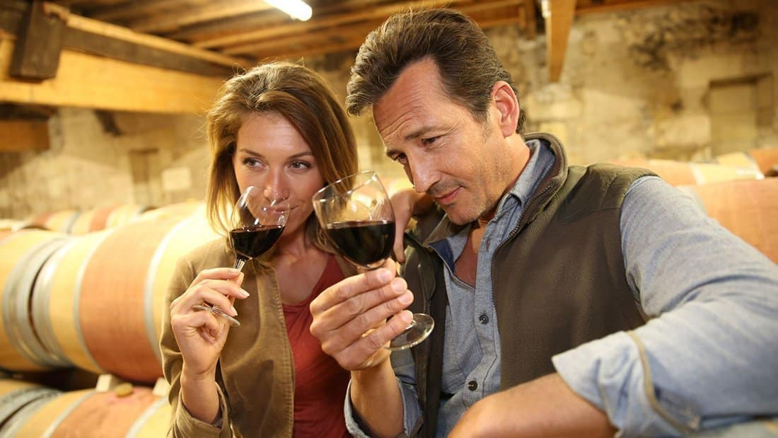 A couple in a barrel room, sniffing and observing the color of the wine before tasting it.