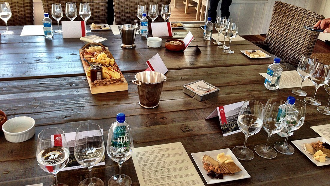 A nice table set with cheeses, crackers, fruits, nuts and glasses for a wine tasting.
