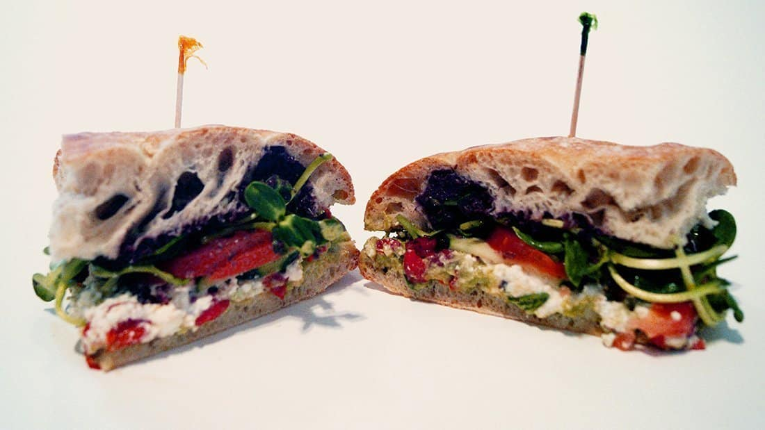 Our veggie sandwich: fresh foccacia with olive tapenade, avocado, fire-roasted red peppers, feta, tomato, sprouts, and cucumbers.