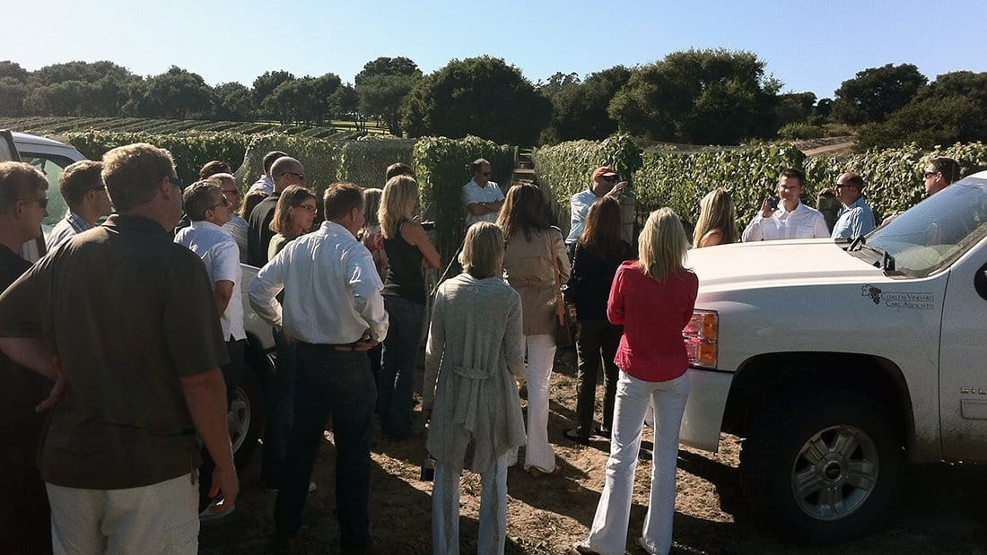 A wine maker with a large group discussing the farming of wine grapes.
